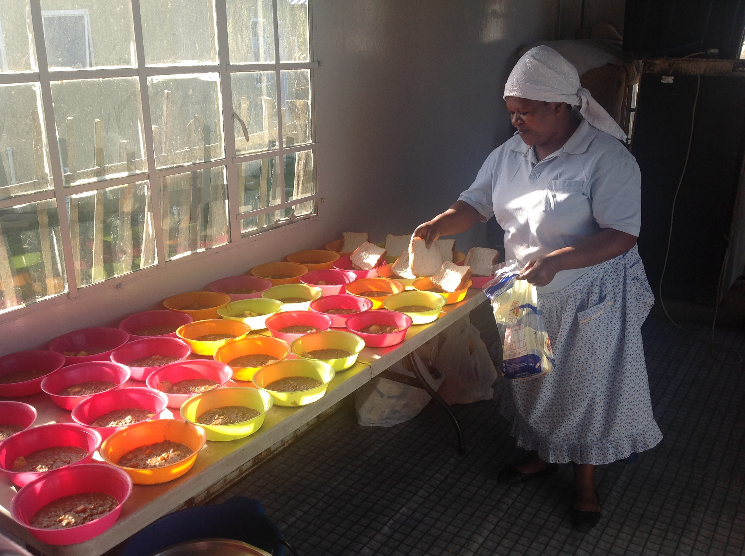 doing a feeding for undernourished children in the tnglani township of knysna, south africa