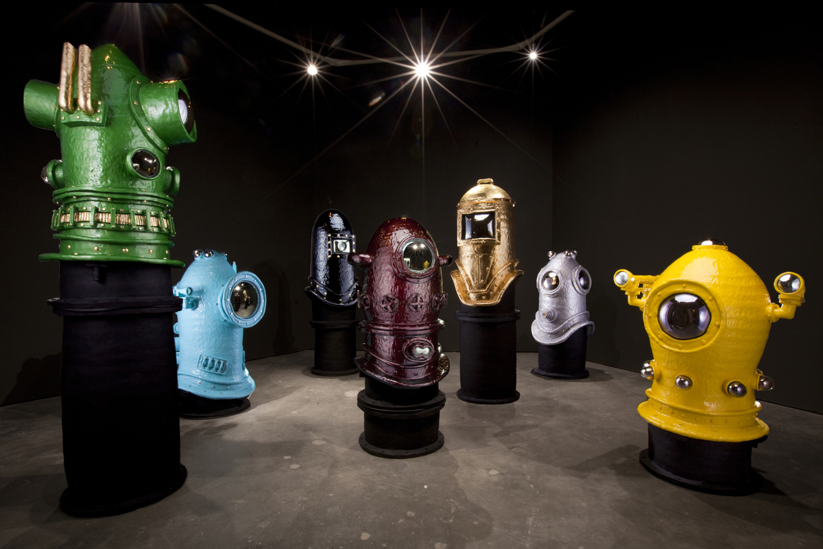 Headspace- Designboom - american artist jacob foran held a solo exhibition entitled 'headspace', a series of large ceramic forms at the university of washington-seattle's 3D4M gallery. arranged in varying heights of five to ten feet tall, the sculptures largely resemble giant diving bells of bright and bold colours.'my work embodies theme of desire and fantasy. influenced by a port-town setting, water and submarine life have become a potent place of metaphor. physical representations of nauticalexploration symbolize a quest for understanding -- an investigation that is inseparable from mymethodology as an artist and my interest in the subconscious. Imagery of diving gear represents armor that provides a stable internal environment in a pressure filled atmosphere…–jacob foranin addition to helmets and armor, foran considers his sculptures to be a form of shelter and private chambers. the diving bells symbolically represent a barrier between one self and the pressures of the outside world. though the sculptures are large enough to physically crawl into, there is no literal point of entry. this, coupled with the playful way in which they are constructed suggest another form of protection--a barrier built with imagination and fantasy.by Erica Kim, Designboom