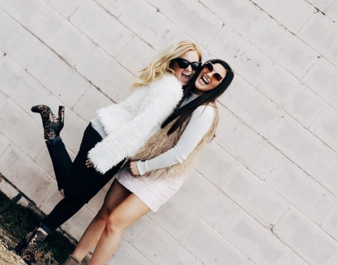 [Photo Description: Paxton (right) and Jenna (left) pose together in front of a white wall.]
