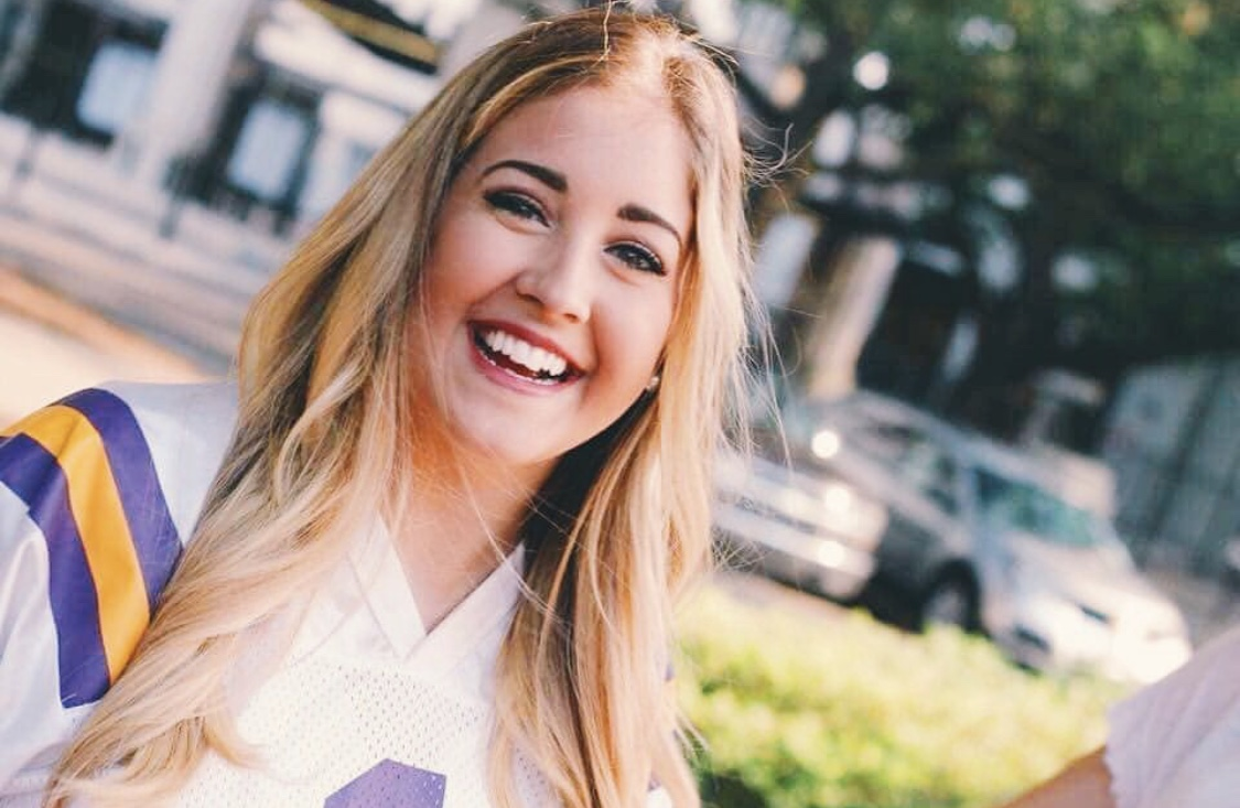 [Photo Description: Brittany wears an LSU football jersey and smiles for the camera.]