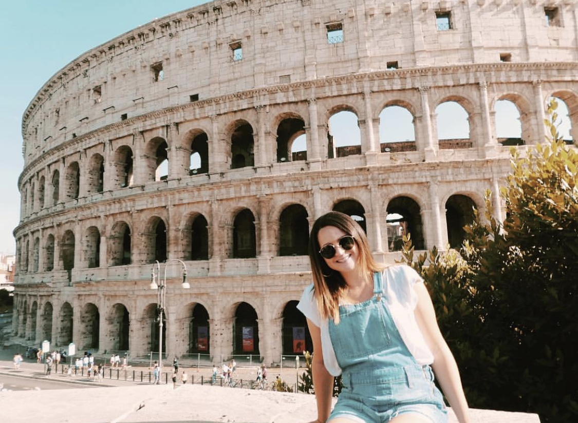 {Photo Description: Ali sits in front of the Colosseum wearing denim overall shorts and a white tee.]