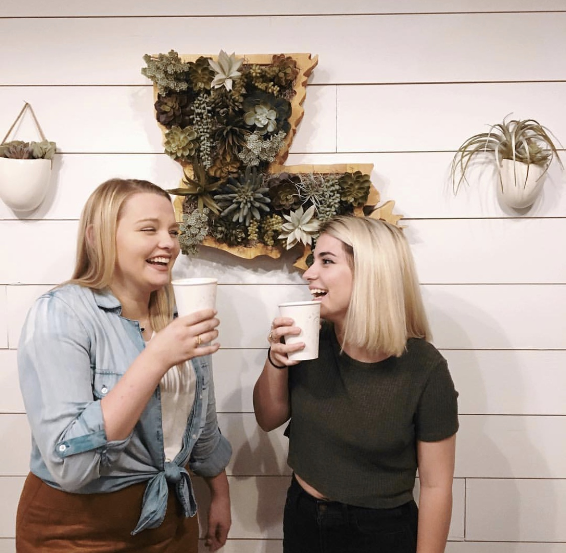 [Photo Description: Catherine (left) and Harper (right) laugh while holding coffee mugs at Light House Coffee.]