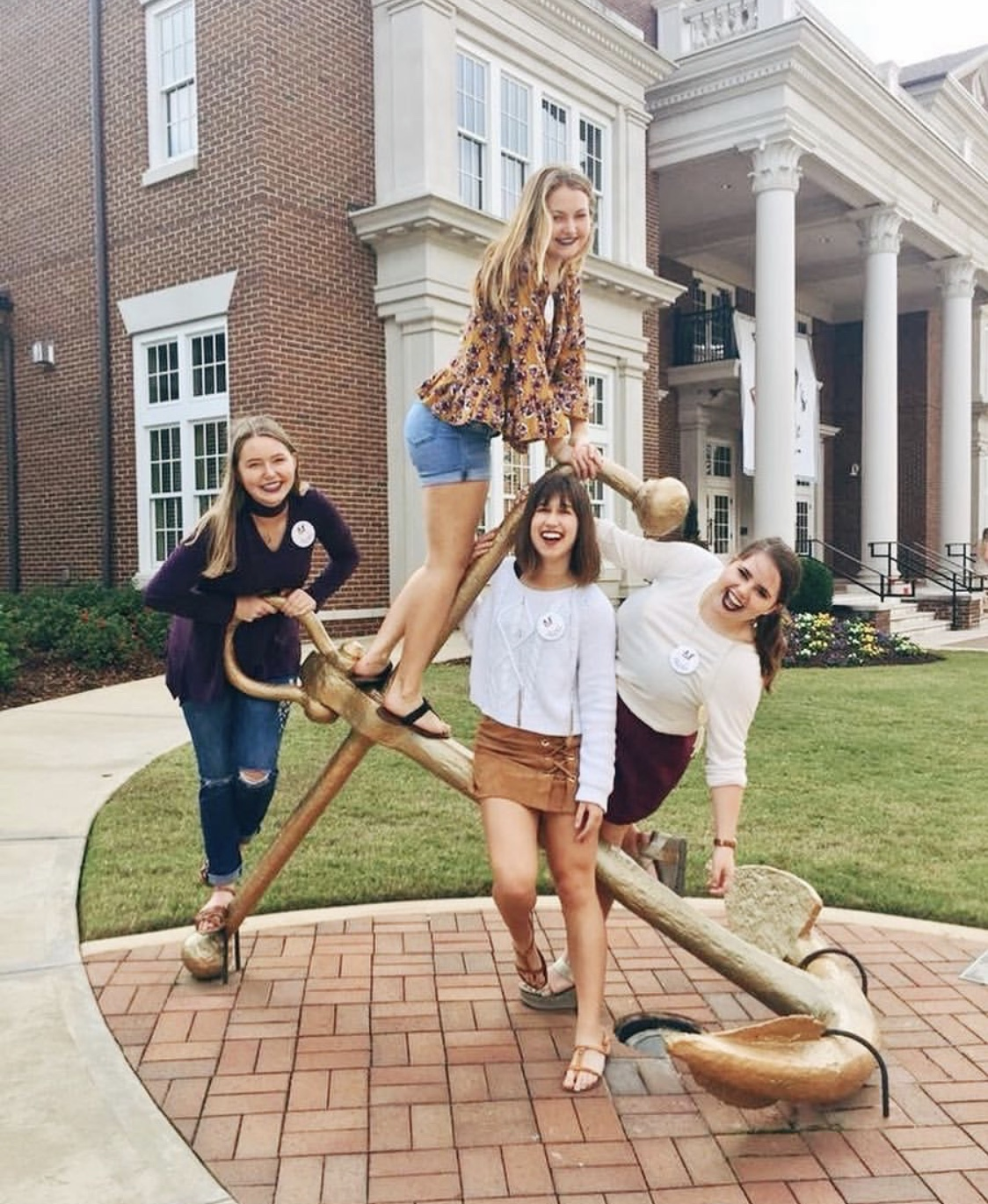 [Photo Description: From left to right, Kelsi, Amber, Lisa, and Merritt pose atop the golden anchor at the University of Alabama.]