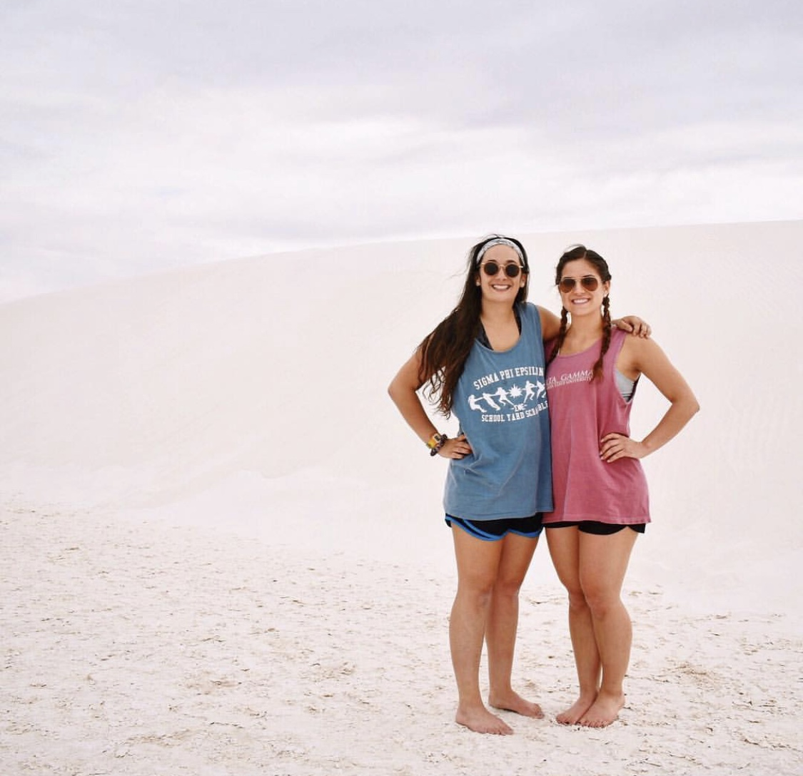 [Photo Description: Gabby (left) stands in the sand sporting a tank top, shorts, and sunglasses.]