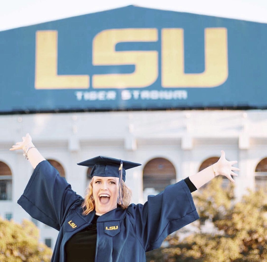 [Photo Description: Carmen has her arms outstretched as she wears her cap and gown outside of LSU tiger stadium.]