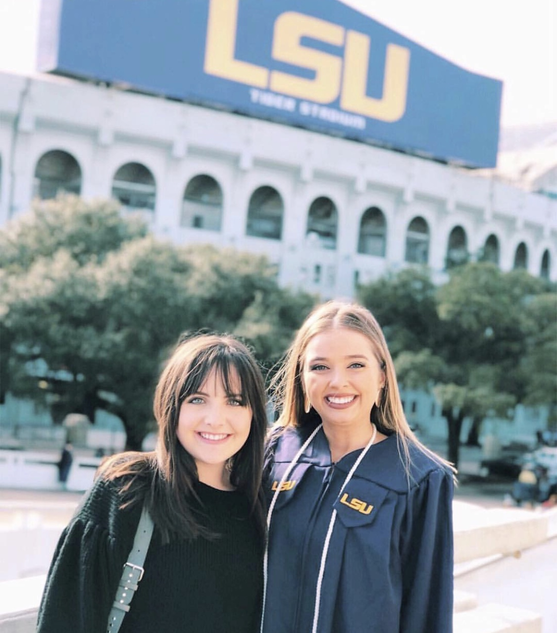 [Photo Description: Callie (right) and Emily (left) smile in front of LSU tiger stadium.]