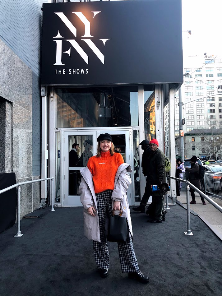 [Photo Description: Katie poses outside of New York Fashion Week while styling an orange turtle neck, gray coat, black and white plaid pants, a black hat, and a black handbag.]