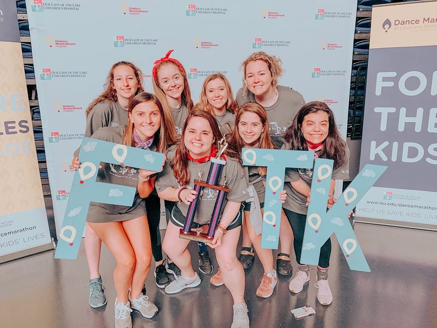 [Photo Description: The DG team for Dance Marathon poses with a trophy and 'FTK' cut out letters that stand for 'For the Kids.']