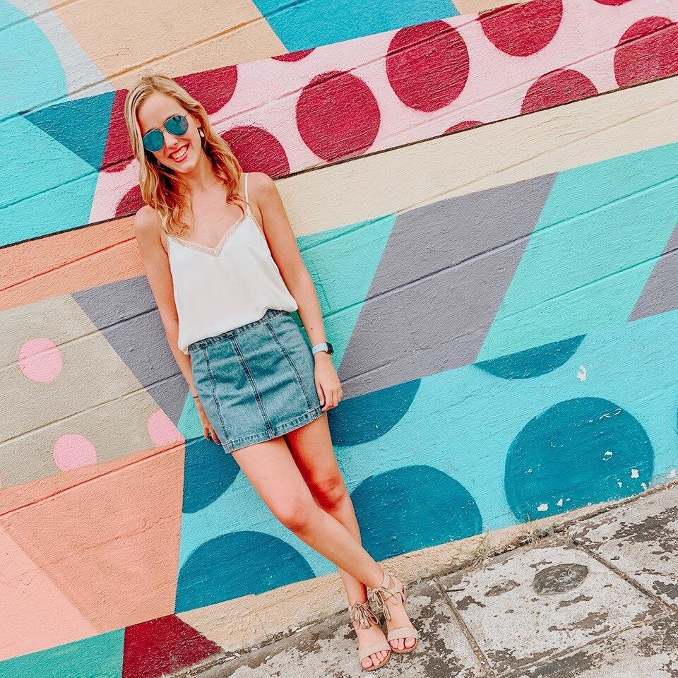 [Photo description: Amelia leaning against a colorfully painted wall in a white top, jean skirt, and sunglasses.]