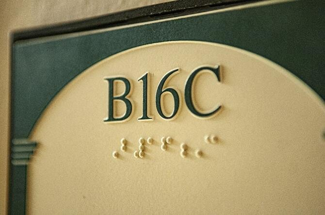 [Photo description: Braille room label in Hodges Hall at Louisiana State University.]