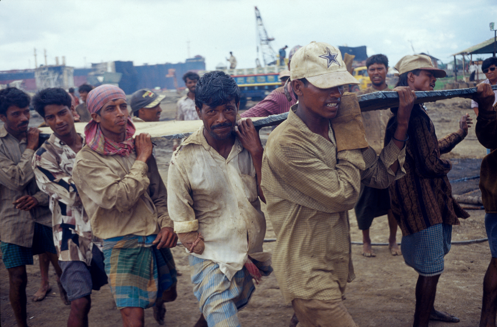 Workers on shipbreaking yards carry heavy pieces of steel scrapped from ships