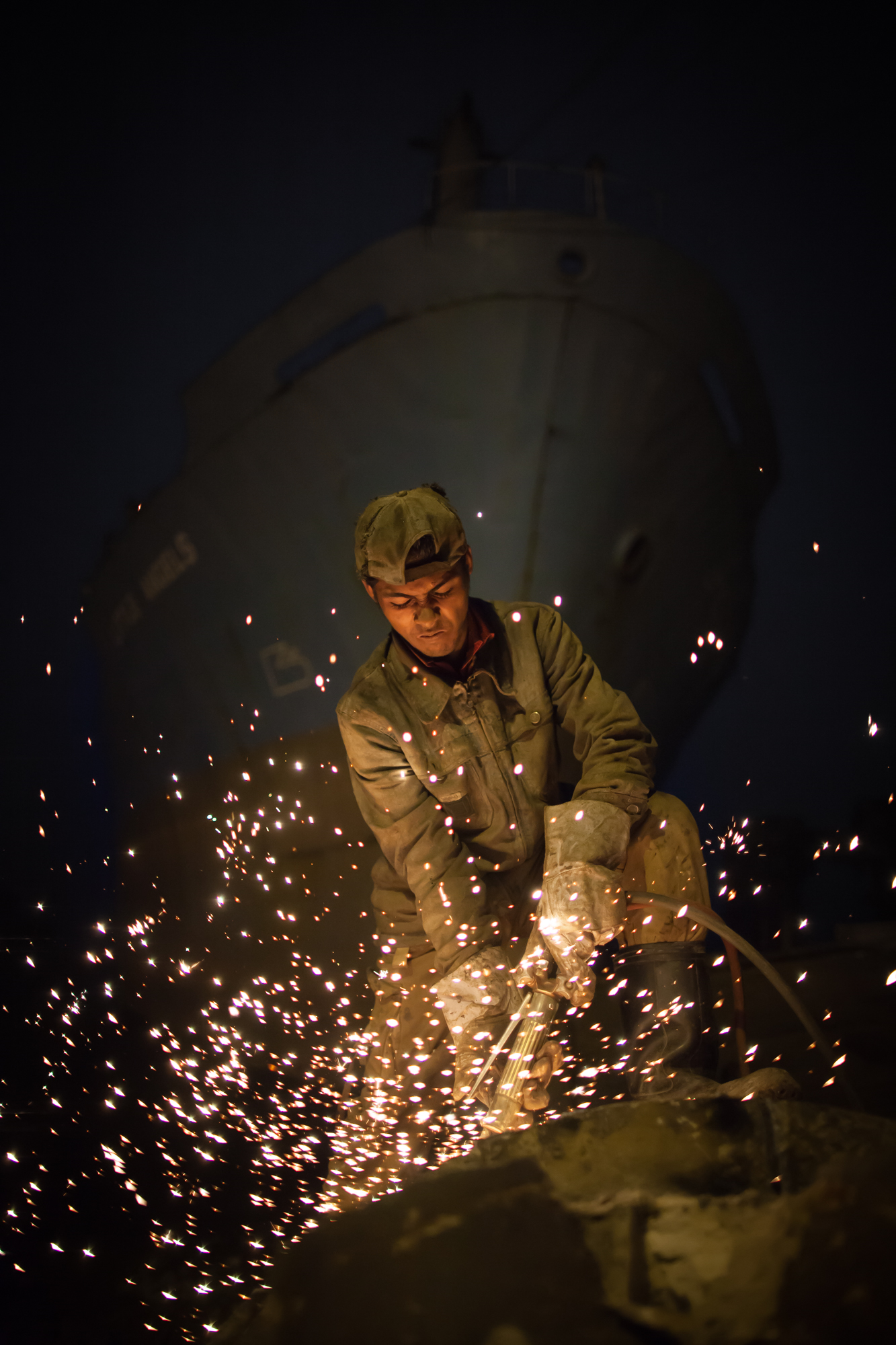 A worker using a blowtorch at night. Copyright Pierre Torset. See more of Pierre's shipbreaking photos    here   .