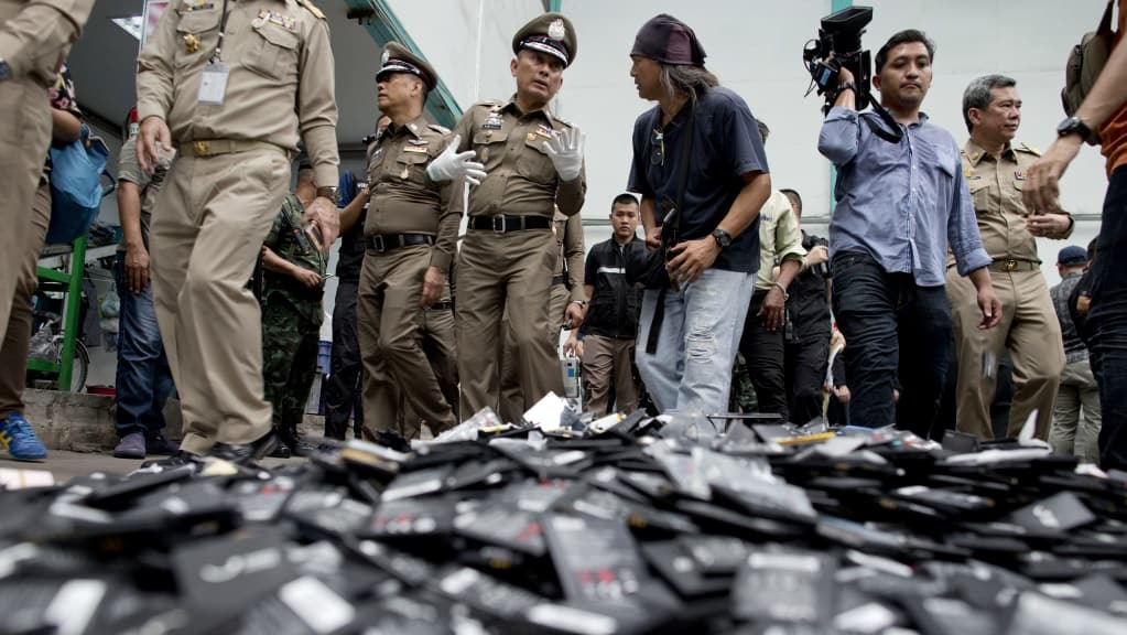 Thai National Deputy Police Chief Wirachai Songmetta, centre with white gloves, law-enforcement officers and journalists walks past a pile of mobile batteries during a raid in Bangkok on Thursday.  Photo:AP