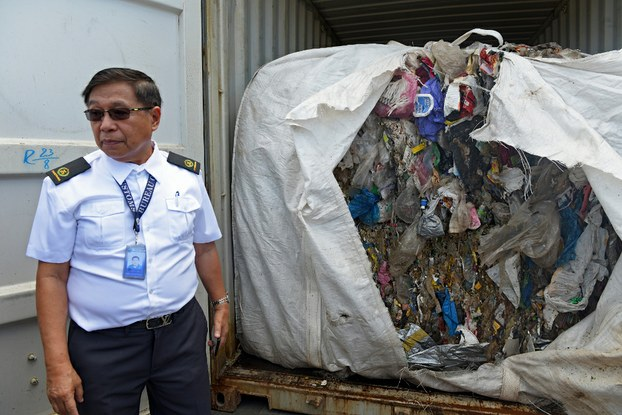 A customs official opens one of dozens of container vans filled with household waste at a port in Tagoloan, the southern Philippines province of Misamis Oriental, Jan. 13, 2019.