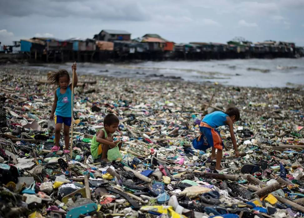 Children collect plastic water bottles among the garbage washed ashore at Manila Bay in the Philippines. Copyright AFP.