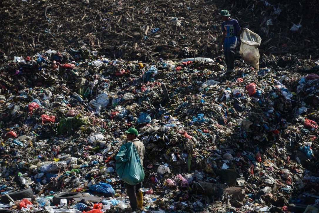 People collect plastic materials at a garbage dump in Banda Aceh, Indonesia, on March 23. The Basel Convention requires its signatories to seek permission from other countries before exporting hazardous and household waste.  (CHAIDEER MAHYUDDIN / AFP/GETTY IMAGES)