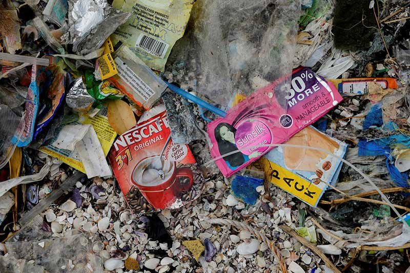 Sachets of Nestle's Nescafe coffee and Unilever's Sunsilk shampoo are pictured amidst a garbage-filled shore on Freedom Island, Paranaque City, Metro Manila, Philippines, July 15, 2019. Picture taken July 15, 2019. REUTERS/Eloisa Lopez