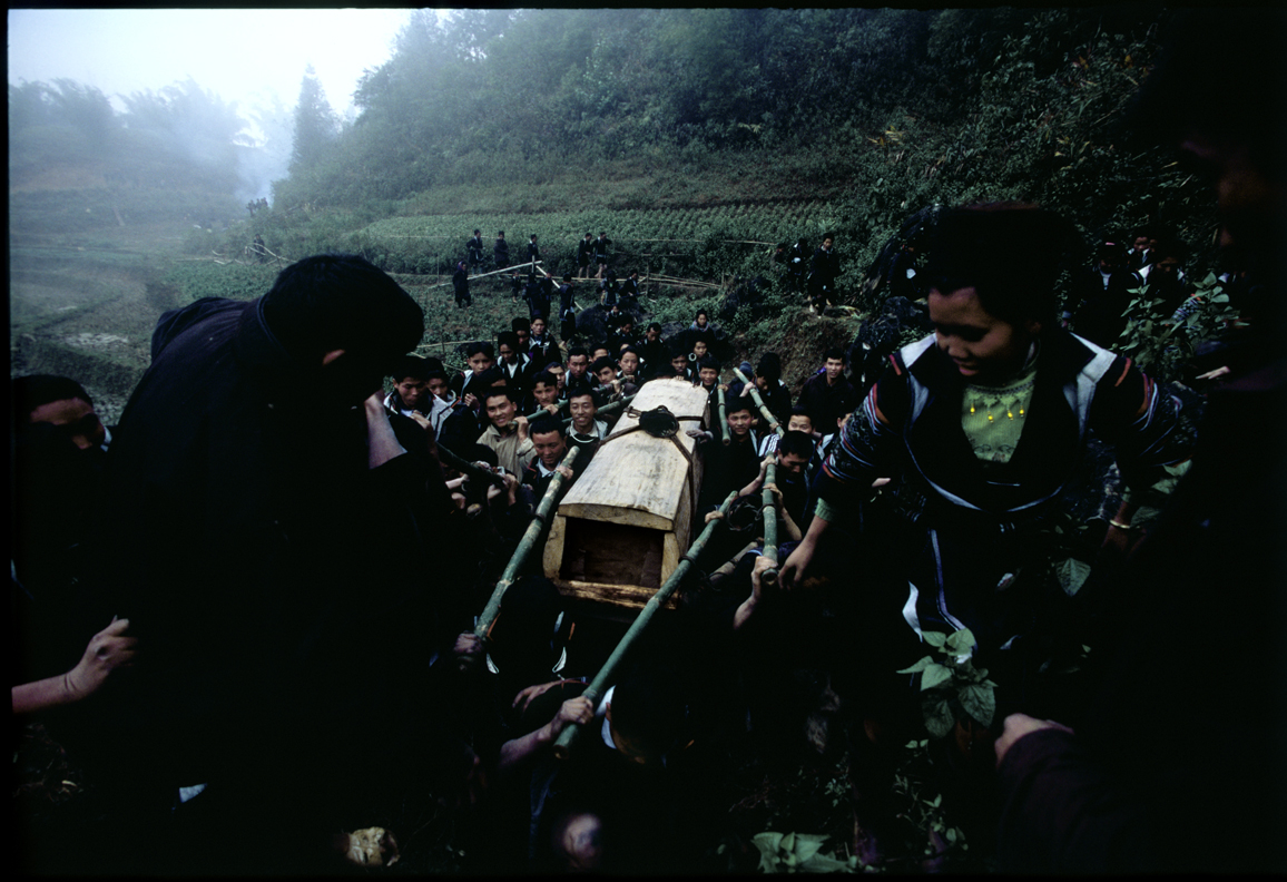 Villagers carrying the coffin up a treacherous hill for burial.