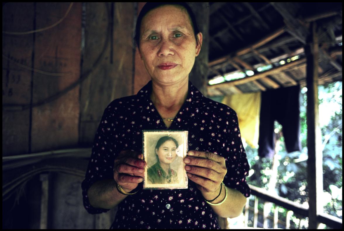Portrait of villager holding up photograph of her young self.