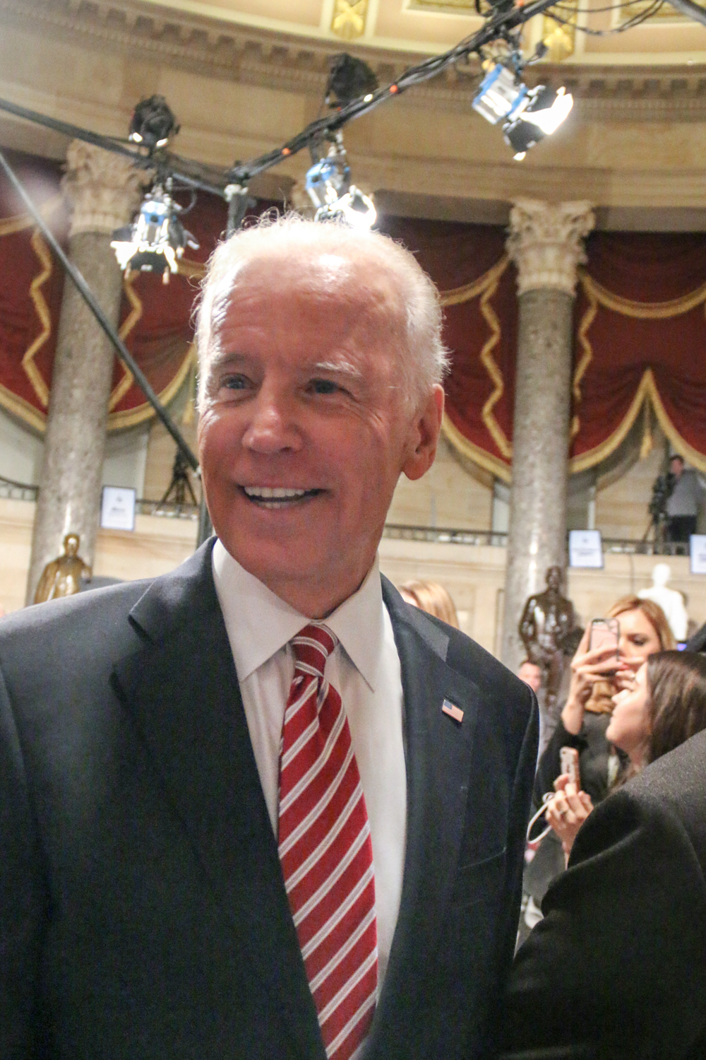 Vice President Joe Biden greets press members with smiles as he walks through Statuary Hall.