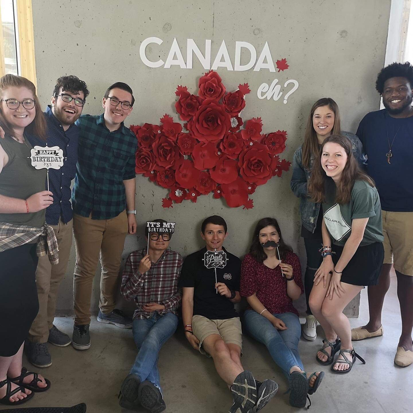 Team in front of Canada sign