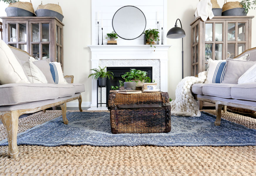 Spring Living Room Update with HomeGoods. Layered rugs, chunky throw, and antique trunk coffee table. - Modern Farmhouse Living Room by Plum Pretty Decor & Design Co.