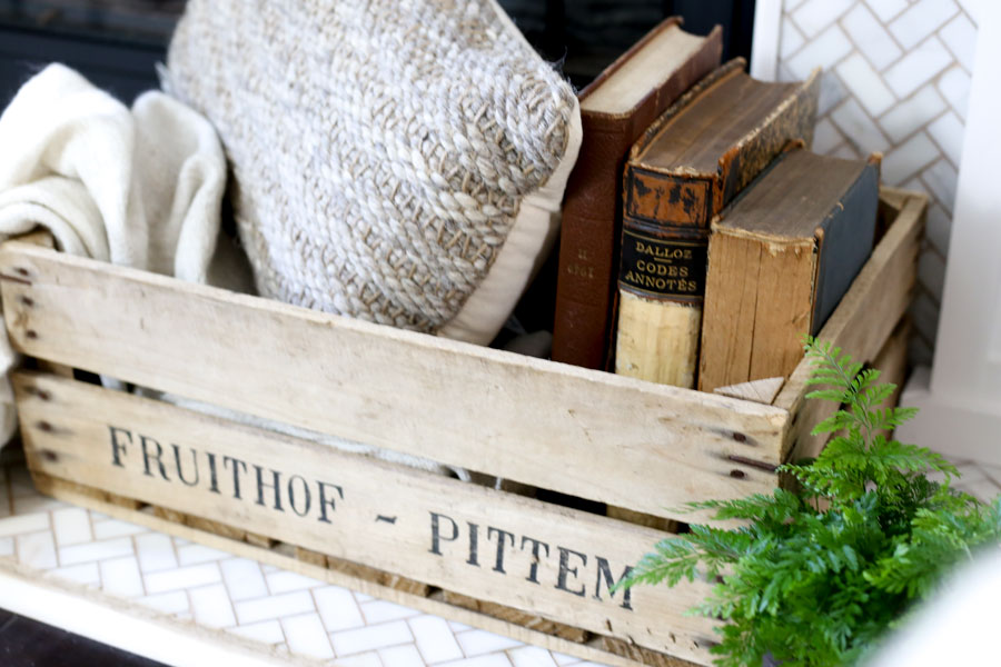 Fireplace decor- Old Books, textured pillow, throw, all in a vintage crate from HomeGoods- Spring Living Room Update with HomeGoods