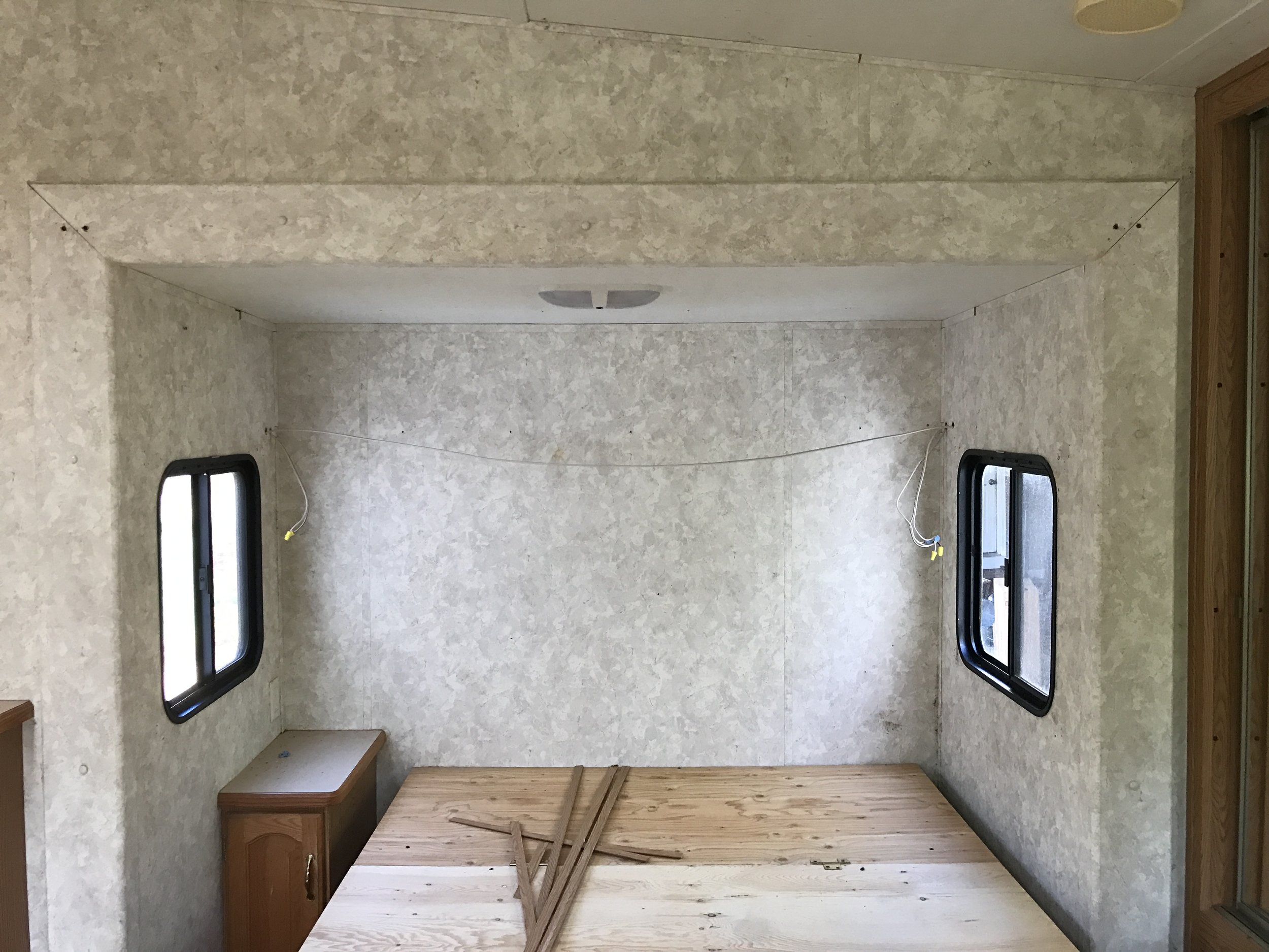 Demo phase of a modern farmhouse camper renovation- bedroom area. Design and renovation by Plum Pretty Decor & Design Co.