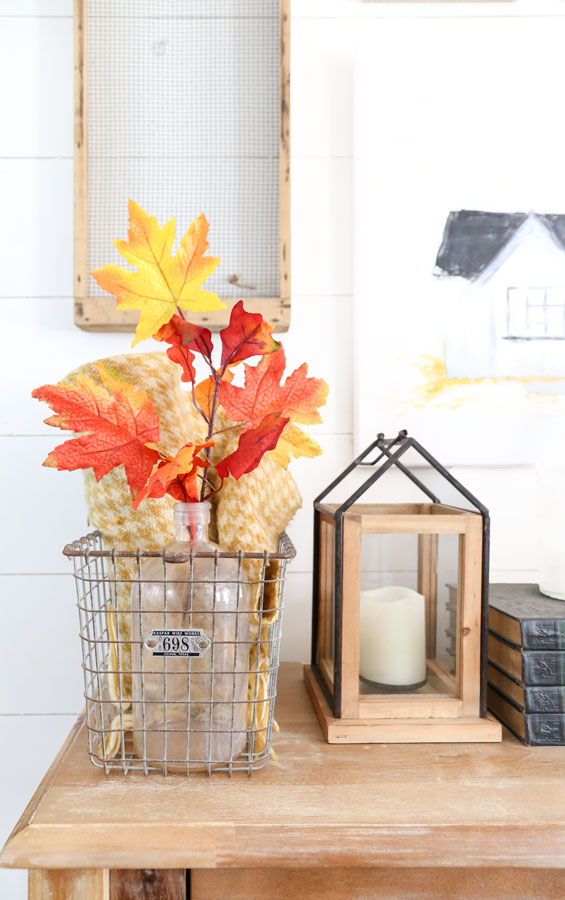 Fall entryway table decor with lantern and leaves in orange, mustard and red colors from Joann. By Plum Pretty Decor & Design