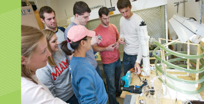 (From left) Emma Witte, Katy Kadlec, Sara Katz, Dan Krzmarzick, Joe Stevenot, Seth Buckwalter, and Bryan Glaenzer check the progress of  the team's photobioreactor, designed to produce hydrogen through the use of cyanobacteria.