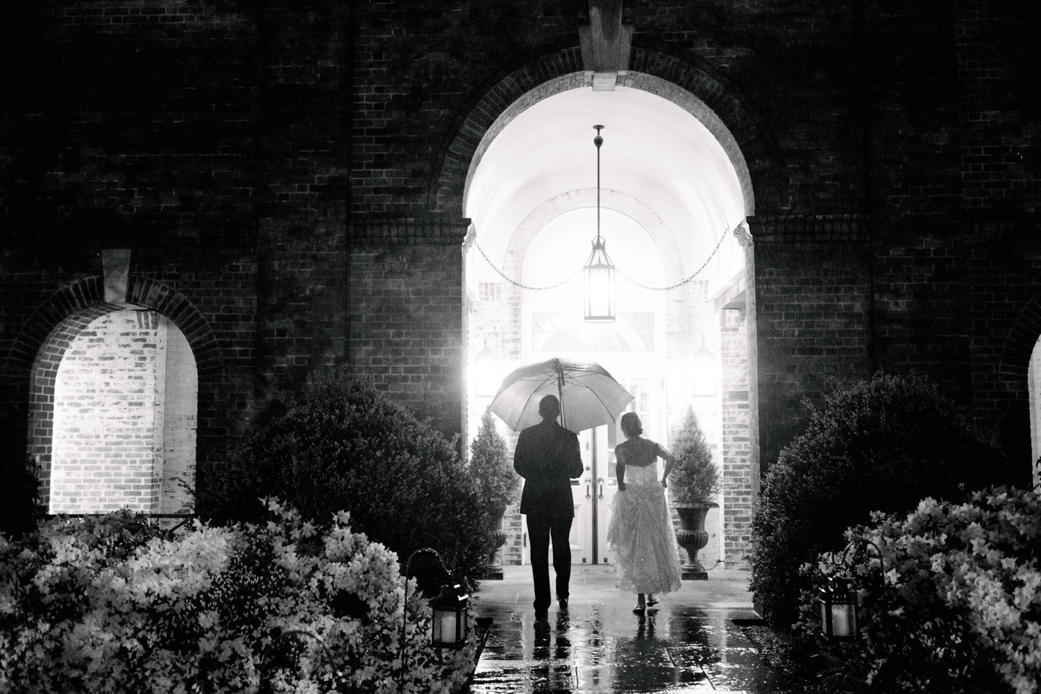 Top of 17 | Number 5 |Jessica & Colin | The New Haven Lawn Club (in the rain!)  Fuji XT2 | Fuji 23 f2  It rained on Jessica and Colin's wedding day... hard. It really didn't stop. Nor did it stop them from having one of the more memorable weddings of my season. Rain is what you make it. It poured on mine and Corey's wedding day, but we had a blast. In this photo, after we had finished some rainy evening portraits, I stayed back as the couple made their way inside. The photos we took were cool, but this quick and candid moment is the clear winner. I love the mood, the drama, the soaking wet pathway, the unlit candles, the way she's hiking her dress...it's everything a photo in the rain should be. If Jessica and Colin werent so willing to come stand in a downpour with me, it never would have happened. I'm so glad they did.