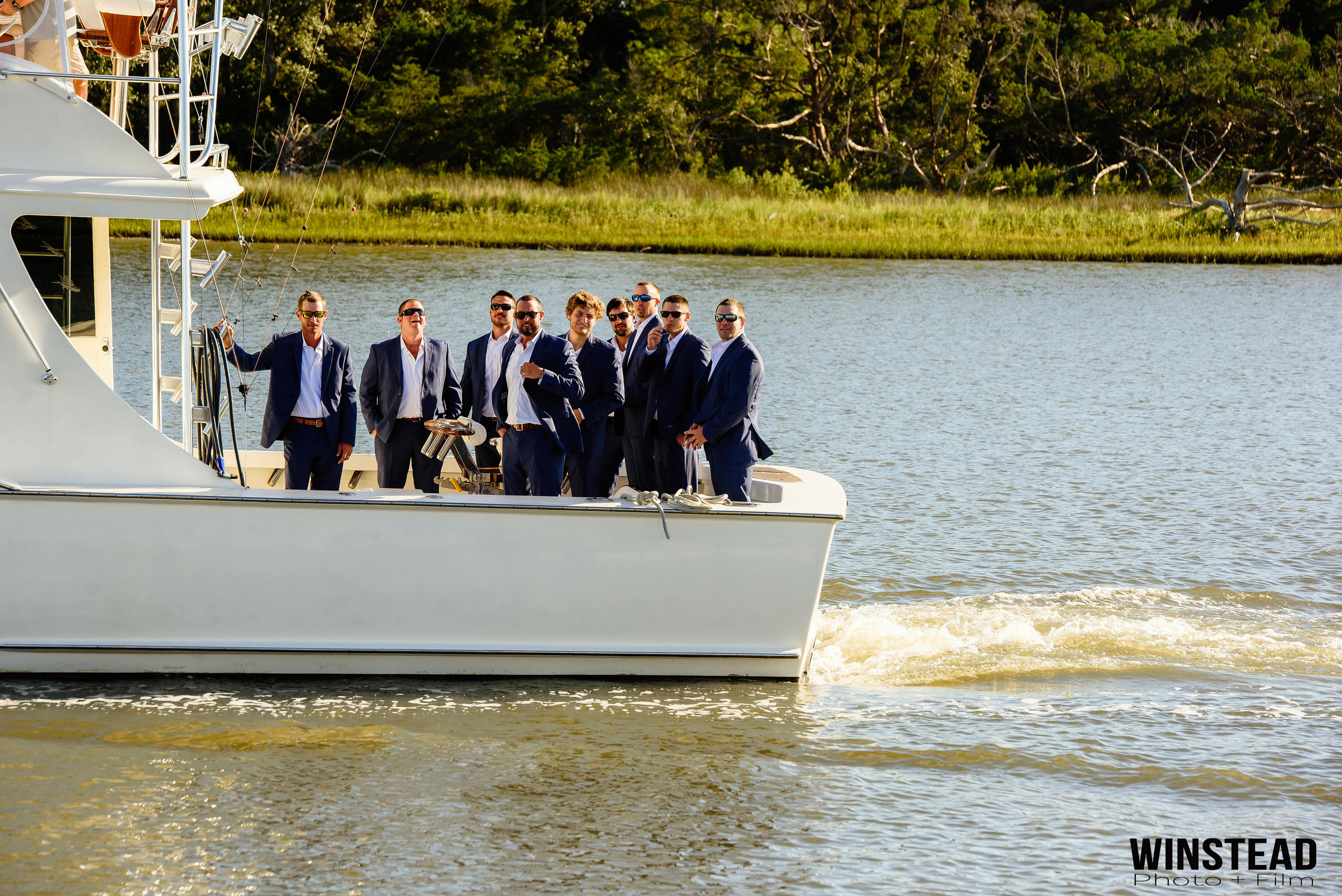 grooms-arriving-on-boat-atlantic-beach-nc-wedding.jpg