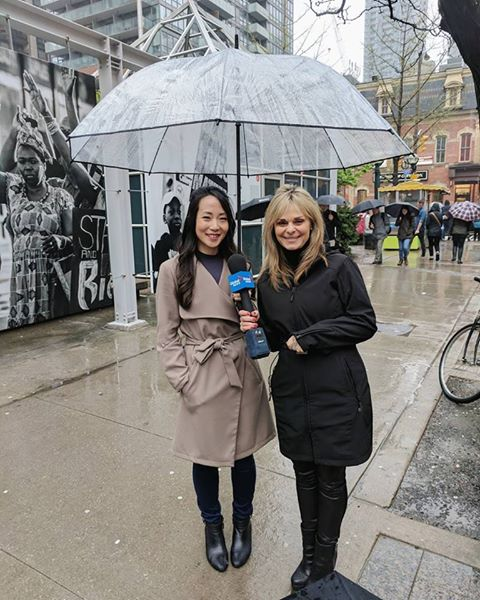 Rebecca Chan sharing rainy day wedding tips under our Large Clear Umbrella on Global News with Susan Hay.