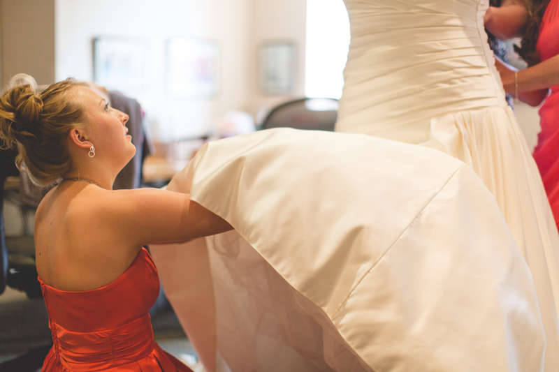 orange county regional history center intimate wedding young bridesmaid fixing wedding dress for bride