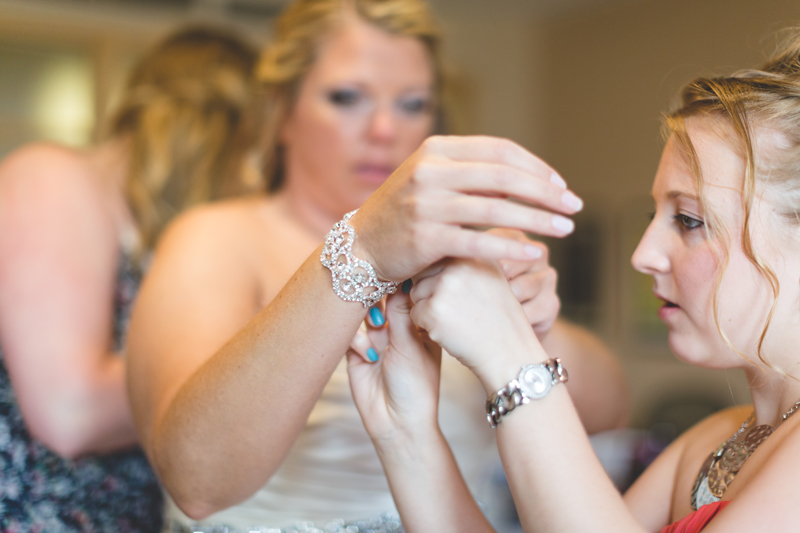orange county regional history center intimate wedding young bridesmaid putting bracelet on bride before wedding