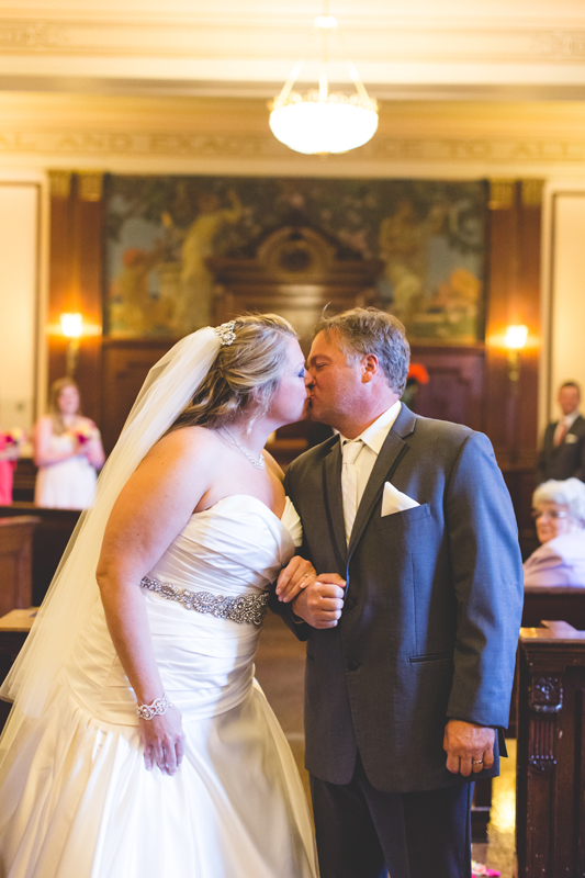 orange county regional history center intimate wedding bride and groom kissing at end of aisle after ceremony in old courtroom