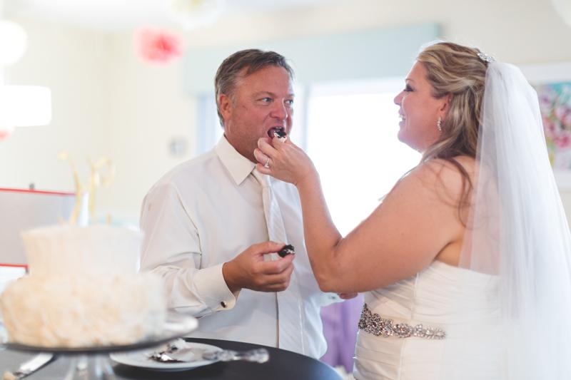 orange county regional history center intimate wedding bride feeding groom wedding cake