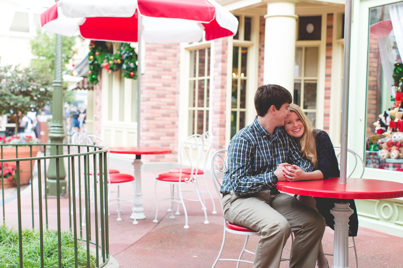 disney engagement photo main street table couple holding hands