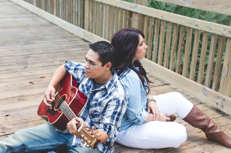 Downtown Celebration Engagement Session Photos - playing guitar to girlfriend