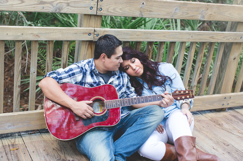 Downtown Celebration Engagement Session Photos - cuddling and listening to guitar
