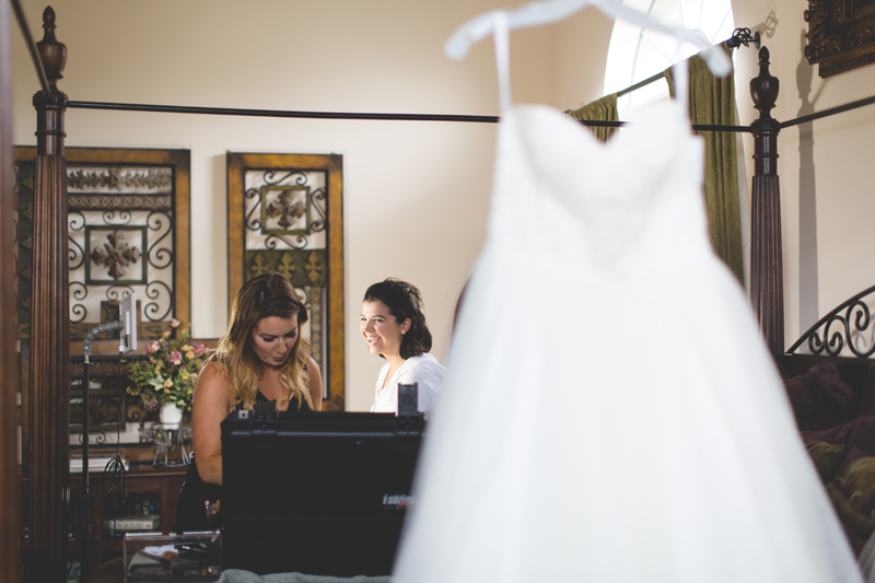 intimate wedding in a home - wedding dress hanging, bride getting makeup