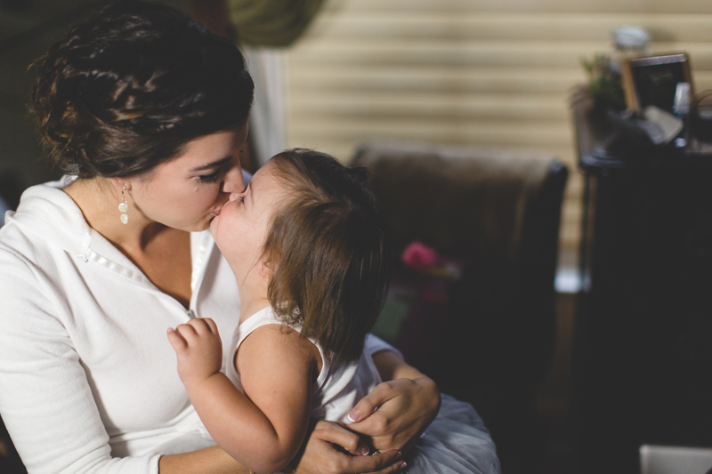 intimate wedding in a house - bride and daughter kissing