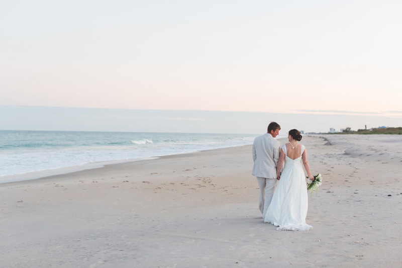 Beach Wedding Photo - bride and groom walking along beach during sunset - destination Orlando wedding photographer - Jaime DiOrio