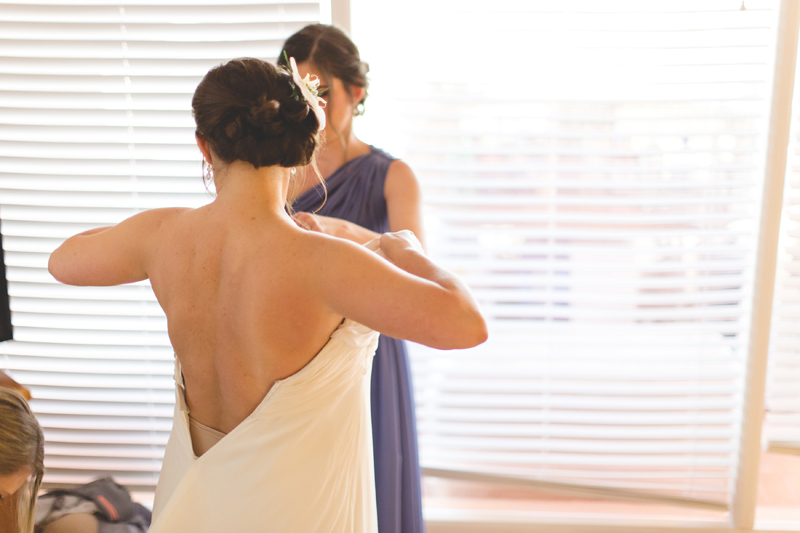Bride putting on wedding dress - Beach Wedding Photos - destination Orlando wedding photographer - Jaime DiOrio
