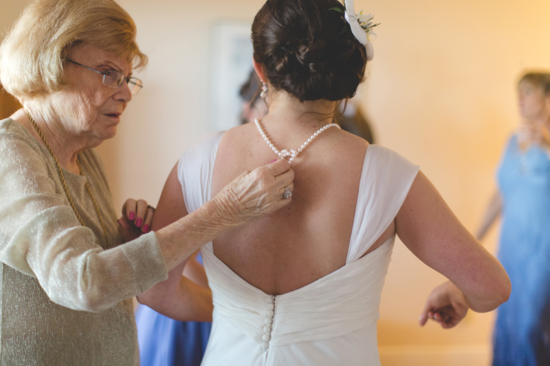 Grandma putting pearls on Bride - Beach Wedding Photos - destination Orlando wedding photographer - Jaime DiOrio