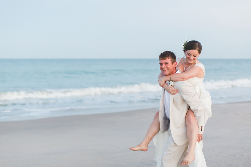 Groom carrying Bride piggyback - Beach Wedding Photos - destination Orlando wedding photographer - Jaime DiOrio