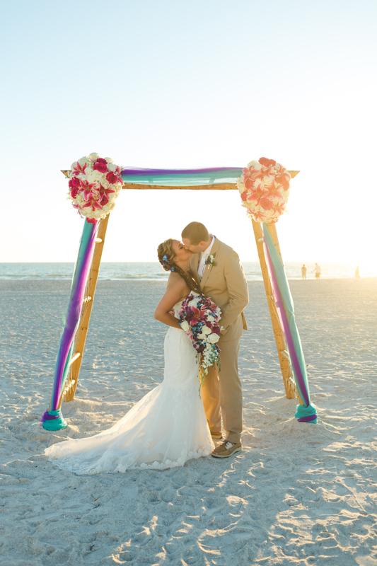 Bride and Groom kissing under bamboo arch - Tradewinds Island Grand Resort beach wedding - st pete beach - Jaime DiOrio Photography - Destination Orlando wedding photographer -  (53).JPG