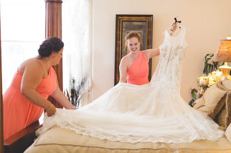 Bridemaids getting wedding dress ready for Bride