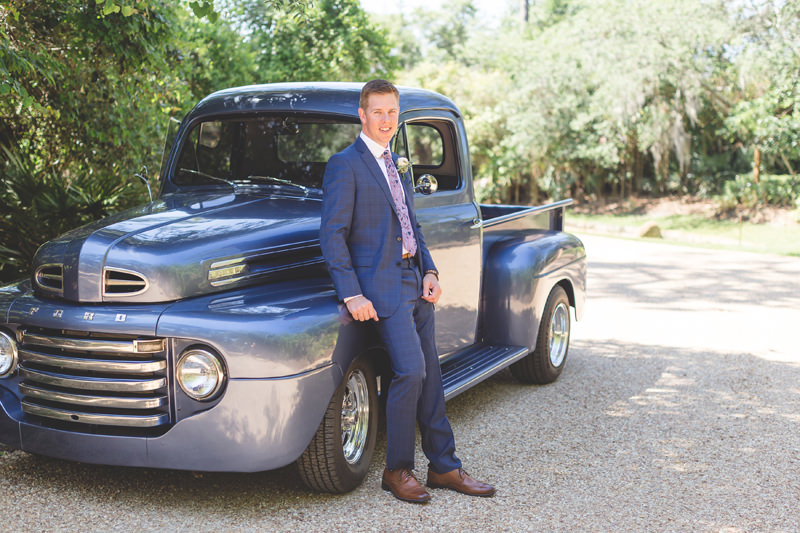 Groom standing beside vintage truck