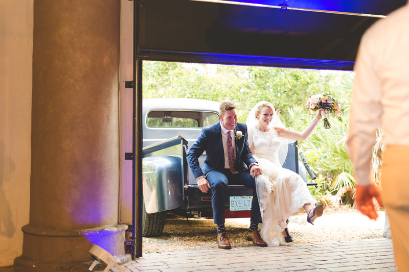 Bride and Groom arriving to wedding reception in blue vintage truck